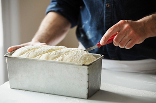 Close up of a baker cutting bread dough in a baking tin.の写真素材 [FYI02706300]