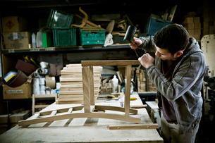 A man working in a furniture maker's workshop assembling a chair.の写真素材 [FYI02706312]