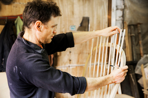 Man standing in a carpentry workshop, working on a wooden chair back.の写真素材 [FYI02706313]