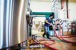Man working in a brewery, connecting hoses to a metal beer tank.の写真素材 [FYI02706315]