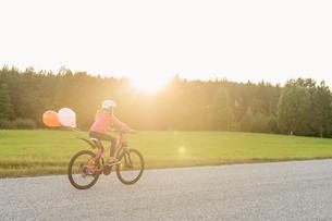 Sweden, Vastmanland, Hallefors, Bergslagen, Girl (10-11) riding bicycle at sunsetの写真素材 [FYI02706330]