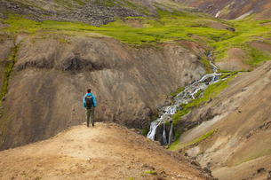 Iceland, Sudurland, Hveragerdi, Reykjadalur, Tourist looking at stream and waterfalls in rocky valleの写真素材 [FYI02706334]
