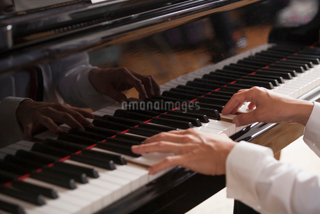 Close up of a pianist's hands, playing on a grand piano.の写真素材 [FYI02706335]