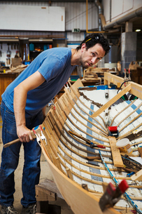 Man standing in a boat-builder's workshop, working on a wooden boat hull.の写真素材 [FYI02706347]