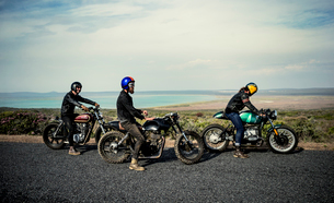 Three men wearing open face crash helmets sitting on cafe racer motorcycles on a rural road.の写真素材 [FYI02706352]