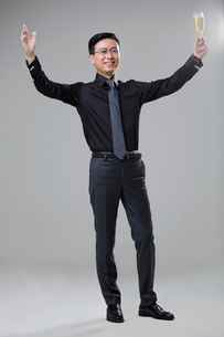 Cheerful mid adult businessman holding a glass of champagneの写真素材 [FYI02706354]