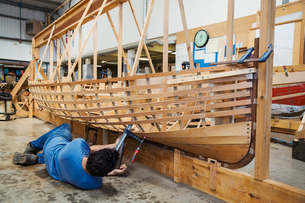 Man lying on floor in a boat-builder's workshop, working on a wooden boat hull.の写真素材 [FYI02706359]