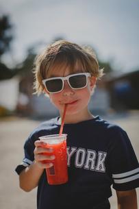 A young boy wearing sunglasses drinking a slushyの写真素材 [FYI02706374]
