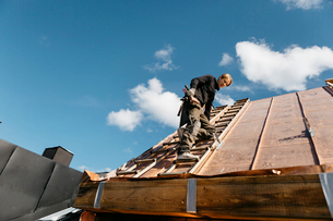 Roofer working on a building in Stockholm, Swedenの写真素材 [FYI02706391]