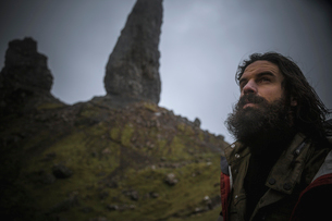 A man standing with a backdrop of rock pinnacles on the skyline towering over him, an overcast sky wの写真素材 [FYI02706397]