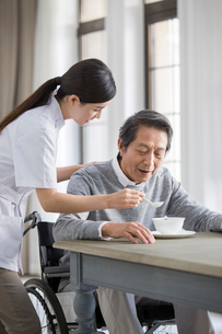 Nursing assistant taking care of senior man in wheel chairの写真素材 [FYI02706414]