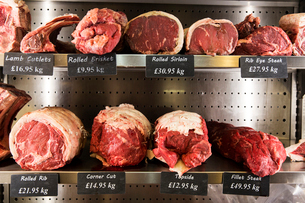Close up of selection of cuts of lamb and beef on metal shelves in butcher shop.の写真素材 [FYI02706429]