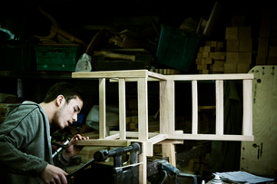 A man working in a furniture maker's workshop assembling a chair.の写真素材 [FYI02706441]