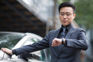 Mid adult businessman checking the time on wristwatchの写真素材 [FYI02706444]