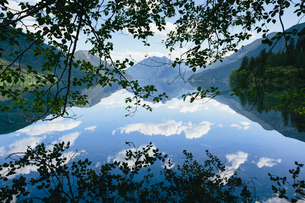 Mirror reflections, the sky and clouds reflected in the surface of the water of Lake Crescent.の写真素材 [FYI02706449]
