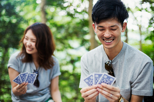 Young woman and man sitting in a forest, playing cards.の写真素材 [FYI02706453]