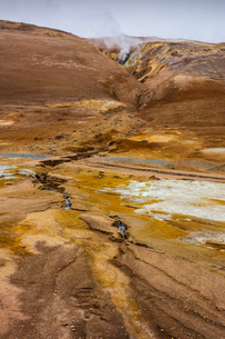 Iceland, Nordurland eystra, Hverarond, Steam over hot springs among rocky mountainsの写真素材 [FYI02706457]