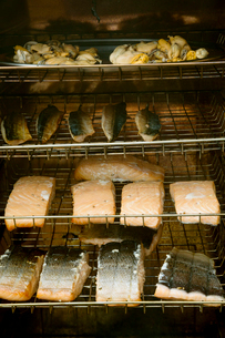 Fish fillets on racks in a fish smoker.の写真素材 [FYI02706466]