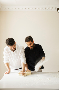 Two bakers standing at a table, kneading bread dough, dusting it with flour.の写真素材 [FYI02706473]