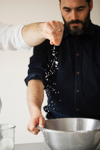 Two bakers standing at a table, baking bread, sprinkling salt into a metal mixing bowl.の写真素材 [FYI02706482]