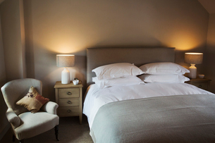 A cosy bedroom decorated in neutral colours, with a double bed and bedside lights on. Hospitality.の写真素材 [FYI02706489]