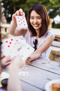 Smiling young woman sitting at a table, playing cards.の写真素材 [FYI02706504]