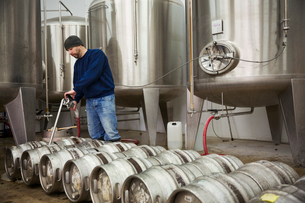 A man filling metal beer kegs from large fermentation tanks in a brewery.の写真素材 [FYI02706508]