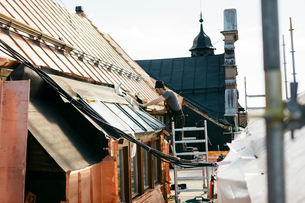 Roofer working on a building in Stockholm, Swedenの写真素材 [FYI02706519]