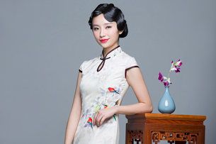 Young beautiful woman in traditional cheongsam with orchidの写真素材 [FYI02706521]