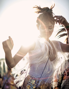Young woman at a summer music festival in a white vest top with fringes with arms raised, dancing amの写真素材 [FYI02706523]