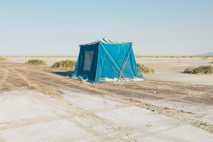 Old muddy blue camping tent in the desert of the Bonneville Salt Flats.の写真素材 [FYI02706526]