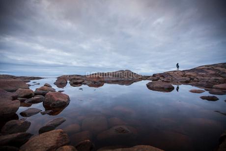 Woman standing by a rock pool in Vasterbotten, Swedenの写真素材 [FYI02706528]