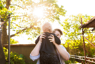 Sweden, Skane, Father picking up son (2-3) in backyardの写真素材 [FYI02706530]