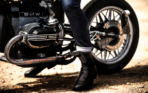 Low section view of man wearing jeans and black leather boots sitting on cafe racer motorcycle.の写真素材 [FYI02706534]