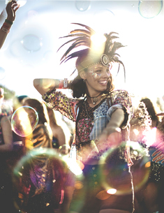Young woman at a summer music festival wearing feather headdress, dancing among the crowd.の写真素材 [FYI02706545]