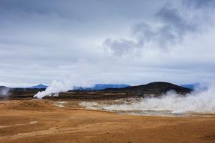 Iceland, Nordurland eystra, Hverarond, Steam over hot springs with mountain range on horizonの写真素材 [FYI02706548]