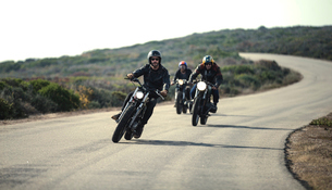 Three men wearing open face crash helmets and sunglasses riding cafe racer motorcycles along rural rの写真素材 [FYI02706551]