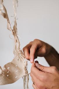 An artist working on an art piece, creating an object with thread.の写真素材 [FYI02706555]