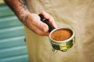 Close up of man with tattoo on his arm holding portafilter for espresso machine.の写真素材 [FYI02706560]