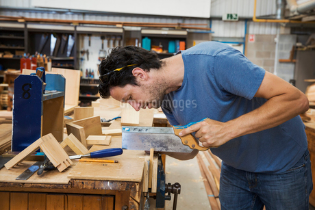 Man working a boat-builder's workshop, sawing small piece of wood with hand saw.の写真素材 [FYI02706561]