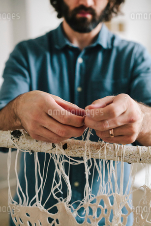 An artist working on an art piece hanging on a frame, knotting and weaving threads.の写真素材 [FYI02706585]