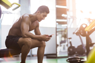 Young man using smart phone in gymの写真素材 [FYI02706588]