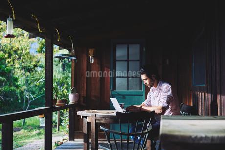 Mid adult man using laptop on verandahの写真素材 [FYI02706592]
