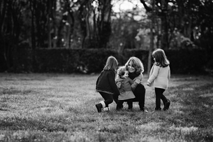 Woman crouching on a lawn with three young girls standing beside her, twin sisters.の写真素材 [FYI02706597]
