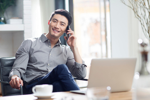 Young man talking on the phone in officeの写真素材 [FYI02706598]
