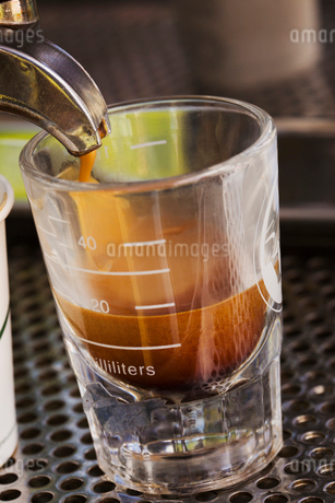 Close up of fresh brewed expresso coffee pouring into a glass from a coffee machine.の写真素材 [FYI02706599]