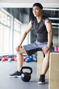 Young man sitting at gymの写真素材 [FYI02706605]