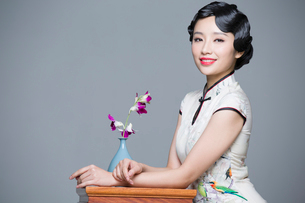 Young beautiful woman in traditional cheongsam with orchidの写真素材 [FYI02706611]