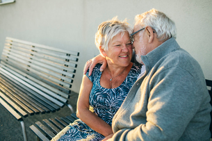 Senior couple hugging on benchの写真素材 [FYI02706612]