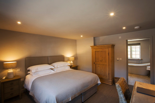 A cosy bedroom decorated in neutral colours, with a double bed and bedside lights on. Hospitality.の写真素材 [FYI02706618]